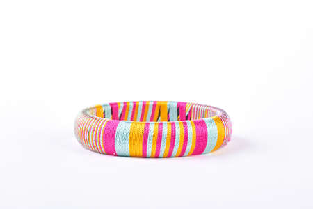 Beautiful colorful bracelet on white background. Bright striped bracelet isolated on white background. Woman modern accessory. Stock Photo