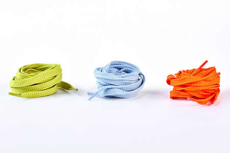 Strings for sport shoes on white background. Green, blue and orange round shoe laces isolated on white background.