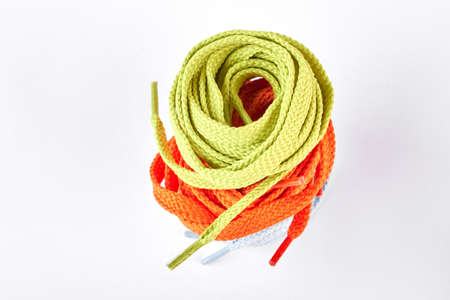 Stack of green and orange shoe laces. Colorful string for sport shoes over white background. Store of shoes accessories. Reklamní fotografie