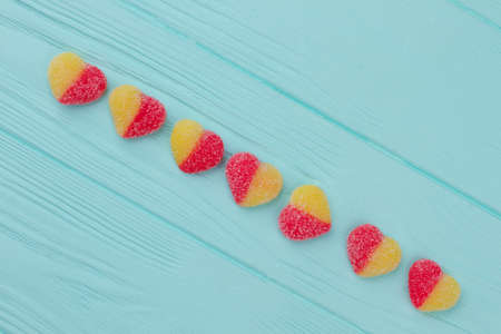 Colorful heart shaped candies. Line from sugary heart shaped candies on blue wooden background, top view. Symbol of love. Valentines Day concept.
