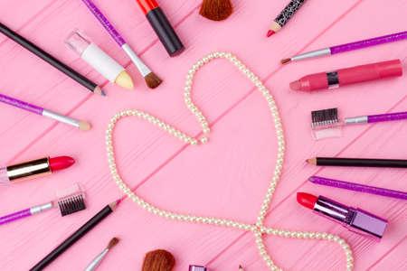 メイクアップアクセサリーコラージュ、トップビュー。木製の背景にハート型の白い真珠のネックレス。バレンタインデーのための化粧品組成物。