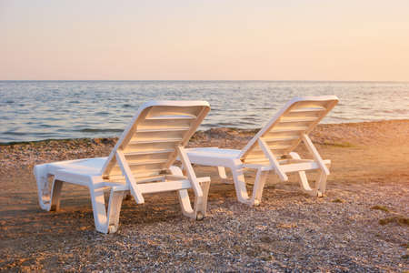 Half-turn view chaise longues on the beach. Beach chaise longues on the morning. Stock Photo