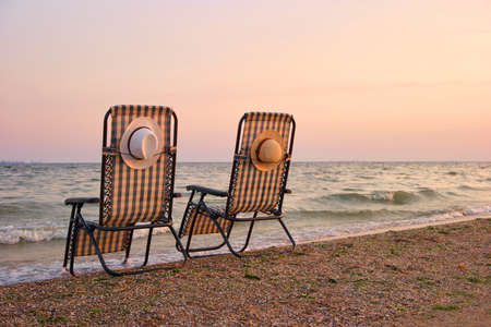 Deckchairs with attached sun hats. Concept of empty left deck chairs beside sea in the evening.