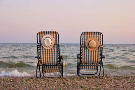 Rear view beach chairs on seashore. Empty beach chairs on sand by the sea, back view. Stock Photo