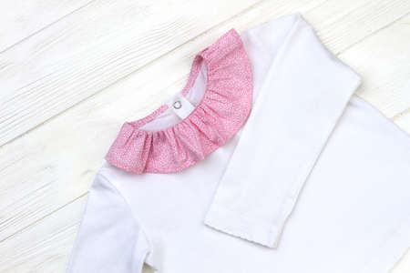 Beautiful white pajama on wooden background. Pink fine pattern collar. New girls clothing collection. Stock fotó