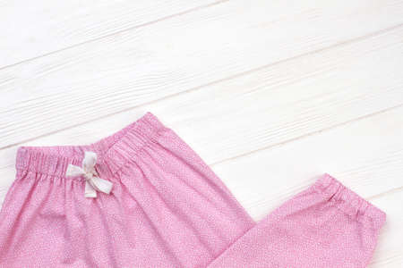 Girls sleepwear on wooden background. Pants made of pink fabric with fine pattern. Elastic waistband and drawstring.