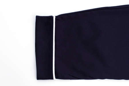 Rolled cuff of pants. Classic model made of blue fabric and decorated with white stripe.