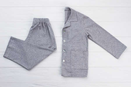 Pajama set on white background. Shirt and pants made of quality gray cotton. Nightwear for young son.