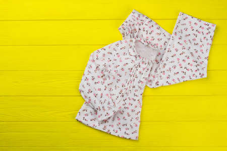 Daughters clothes on yellow background. Adorable top with collar and ruffles and loose pants. Floral print and fashionable design.