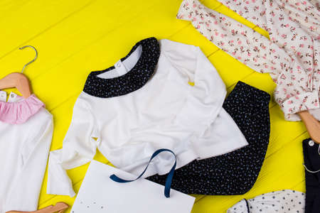 Childrens clothes on yellow table. Mess in girls room. Pajamas and loungewear.