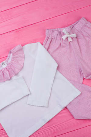 Girls pajama on pink table. Long sleeve t-shirt with ruffle collar and pants with fine pattern. Nightwear for comfy rest. Stock fotó