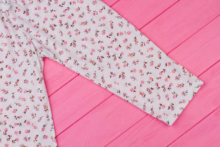 Close up on pajama pants. Sleeping garment decorated with flower pattern. Pink wooden shelf of a clothing store. Foto de archivo
