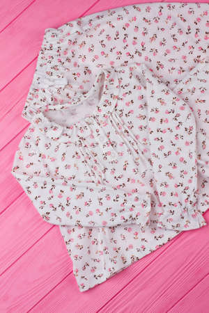Girls sleepwear on pink table. White fabric with fine flower pattern. Simple design with cute ruffles. Stock Photo