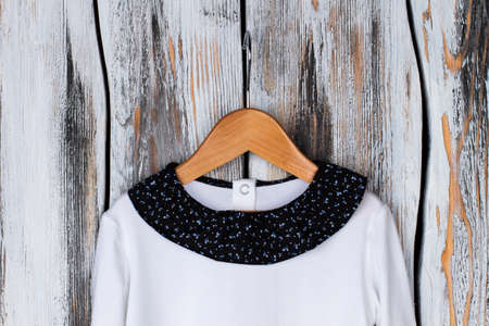 White top with round neckline. Black collar ornated with blue floral print. Choosing a pajama for little daughter.