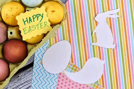 Easter card on Easter painted eggs. Paper Easter cutouts on colorful patterned paper sheets. Congratulations on Easter holidays. Stock Photo