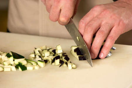 Courgette dicing closeup. Male hands dicing a courgette into small pieces, close-up.