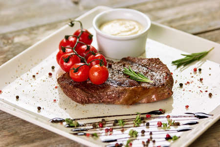 Ribeye steak with madagascar pepper sauce. Ribeye steak with madagascar pepper sauce in white pot, tomatoes and rosemary.