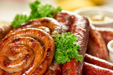 Juicy sausage spirals, closeup. Juicy sausage spirals and garnish.