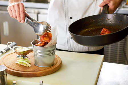 Hot chicken wing bucket filling using kitchen utensil tongs. Chef transfering chicken pieces from pan to metal bucket. Banco de Imagens