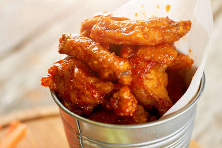 Juicy fried chicken meat pieces in sause, close up. Closeup hot chicken wings in aluminium bucket. Stock Photo