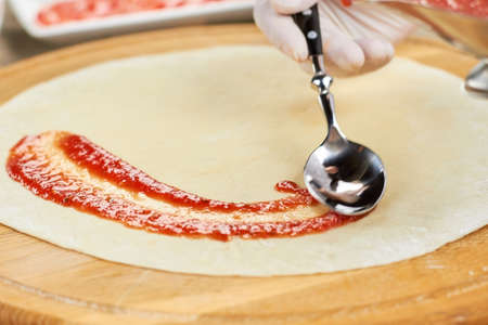 Tomato sauce smearing by spoon. Ketchup smearing on pizza dough.