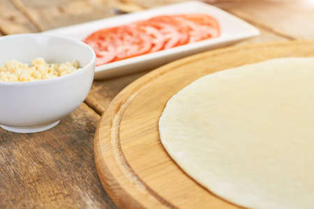 Pizza dough and side dish. Round dough sheet.