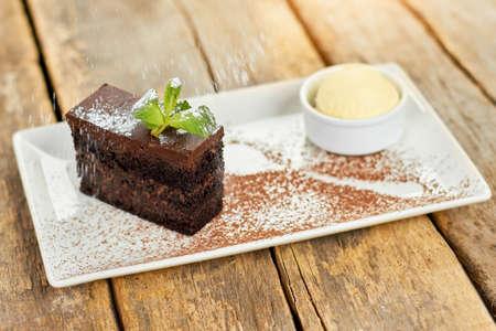Rain of flour on cake. Black belgian cake flouring with white powder. Stock Photo
