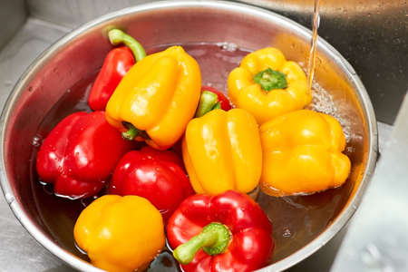 Red and yellow bell peppers in a basin of water, close up. Metal bowl with bell peppers. Stock Photo