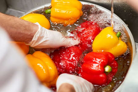 Close up chef hands washing papriks with water stream. Chef rinsing fresh vegetables under tap water.