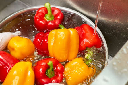 Wet bell peppers into bowl under water stream. Flowing water on bell peppers.