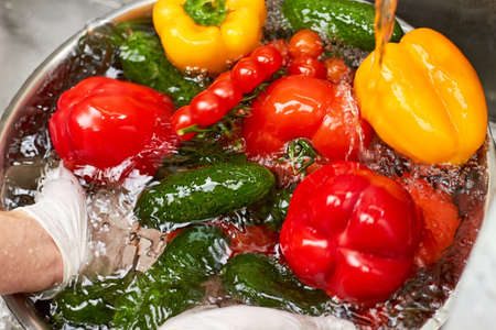 Feche acima da pilha dos vegetais em uma bacia do metal completamente de água. Água que flui em vegetais.