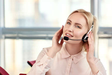 Portrait of businesswoman talking on the headset phone. Female customer support operator with headset and smiling in bright room. Holding headset using both hands. Stock Photo