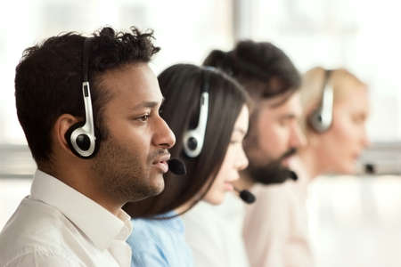 Black call center operator with colleagues. Side view of line of call centre employees are smiling and working on computers. Standard-Bild