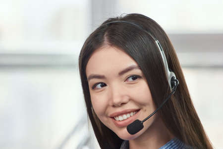 Portrait of a young asian female customer service operator. Young japaneese beautiful call center female operator portrait.