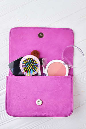 Women bag stuff on wooden background. Female pink bag with cosmetics products and smartphone, white wooden background.