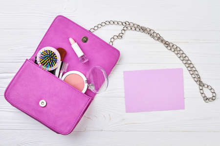 Clutch with female makeup accessories. Flat lay of pink leather woman bag open out with cosmetics, accessories and smartphone. Blank paper card for text.