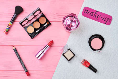 Cosmetics essentials on colorful background. Lipstick, eyeshadows, perfume, nail polish, blusher. Makeup beauty care accessories, flat lay. Stock Photo
