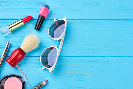 Cosmetics and accessories, blue background. Make up cosmetics products and sunglasses on wooden table, copy space. Summer beauty essentials. Stock Photo