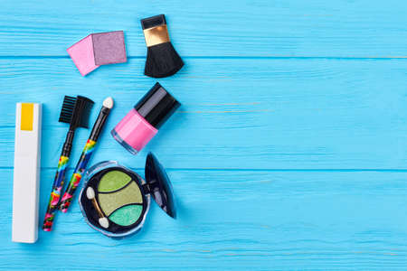 Fashion cosmetics items, copy space. Decorative cosmetics products on blue wooden background. Female beauty objects.