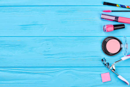 Pink color cosmetics border, copy space. Colorful decorative cosmetics products on blue wooden background, space for text.