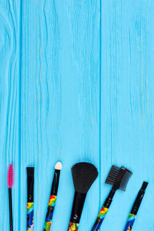 Brushes for makeup on color background. Set of professional make up brushes on wooden background, copy space. Beauty equipment set. Stock Photo