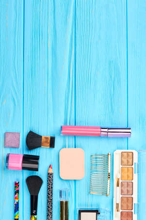 Cosmetic essentials on wooden background. Cosmetics and beauty accessories on blue woden table, copy space.
