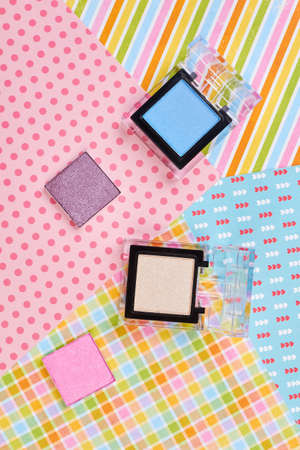 Set of four colors eyeshadows, top view. Flat lay decorative cosmetics products on patterned paper background.