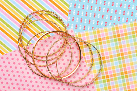 Set of golden bracelets, colorful background. Female bangles on patterned paper background. Woman stylish jewelry.