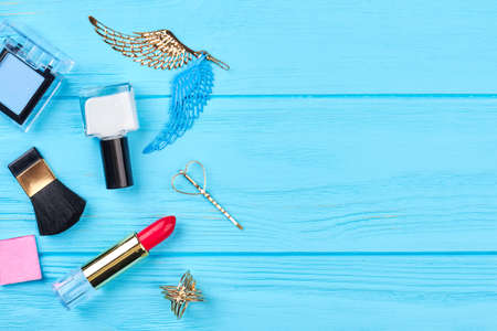 Female cosmetics and accesories. Lipstick, eyeshadows, nail polish and accessories on blue wooden background, space for text. Stock Photo
