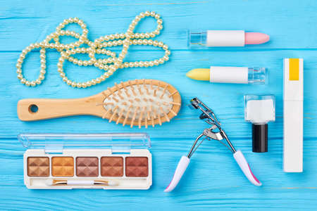 Flat lay cosmetics and accessories. Women makeup products and equipment, blue wooden background. Femininity and fashion concept. Stock Photo