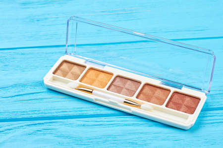 Brown color eyeshadows palette. Set of nude eyeshadows on blue wooden background. Fashion make up accessory. Stock Photo