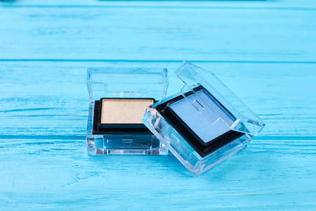 Blue and beige eyeshadows, blue background. Fashion color eyeshadows in compact box, wooden background. Cosmetics make up objects.