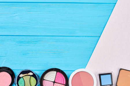 Eyeshadows set on wooden background. Face blushers and eyeshadows on color background, space for text. Decorative cosmetics objects.