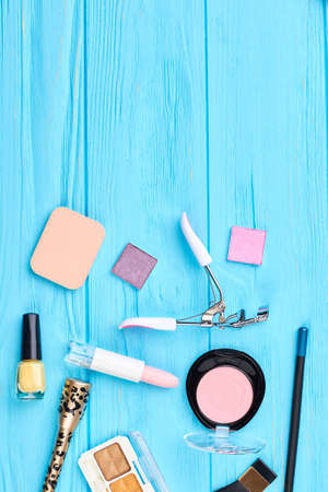 Cosmetics for natural makeup, top view. Decorative cosmetics products and tools for makeup on wooden background, copy space. Stock Photo